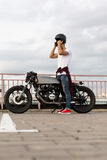 Brutal man near his cafe racer custom motorbike. Handsome rider man with beard and mustache posing while take off black moto helmet near classic style biker stock photo