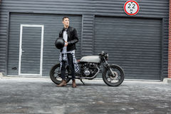 Brutal man near his cafe racer custom motorbike. Stock Photos
