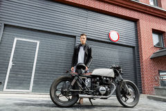 Brutal man near his cafe racer custom motorbike. Royalty Free Stock Images