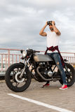 Brutal man near his cafe racer custom motorbike. Handsome rider guy with beard and mustache posing while put on protection glasses near classic style biker cafe stock image