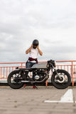 Brutal man near his cafe racer custom motorbike. Handsome rider guy with beard and mustache posing while take off black moto helmet near classic style biker stock photo