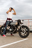Brutal man near his cafe racer custom motorbike. Handsome rider guy with beard and mustache put on black moto glasses and ready to go on classic style biker royalty free stock photos