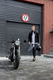 Brutal man near his cafe racer custom motorbike. Stock Image