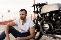 Brutal man near his cafe racer custom motorbike. Rider man with beard and mustache in clear white t-shirt sit near his classic style biker cafe racer motorcycle stock photography