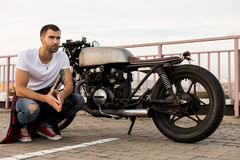 Brutal man near his cafe racer custom motorbike. Rider guy with beard and mustache in clear white t-shirt sit near his classic style biker cafe racer motorcycle royalty free stock photo