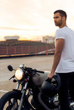 Brutal man near his cafe racer custom motorbike. Sporty biker handsome rider guy in white t-shirt go travel on classic style cafe racer motorbike on rooftop at stock image