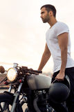 Brutal man near his cafe racer custom motorbike. Sporty biker handsome rider guy in white t-shirt hold black helmet near classic style cafe racer motorbike at royalty free stock photos