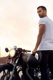 Brutal man near his cafe racer custom motorbike. Sporty biker handsome rider male in white t-shirt go travel on classic style cafe racer motorbike on rooftop at royalty free stock photo