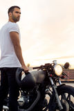 Brutal man near his cafe racer custom motorbike. Stock Photo