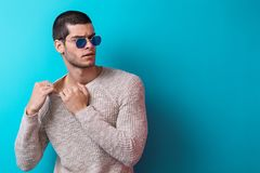 Handsome man  portrait wearing sunglasses. Brutal man portrait wearing sunglasses on blue studio background. Sensual male wearing sweater and jeans, ready to Stock Images