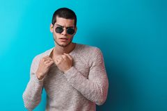 Handsome man portrait wearing sunglasses. Brutal man portrait wearing sunglasses on blue studio background. Sensual male wearing sweater and jeans, ready to take Royalty Free Stock Photos