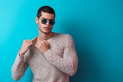 Man wearing sunglasses. Brutal man portrait wearing sunglasses on blue studio background. Sensual male wearing sweater and jeans, ready to take off his pullover Royalty Free Stock Photography
