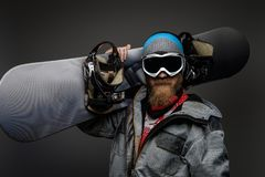 Brutal man with a red beard wearing a full equipment holding a snowboard on his shoulder, isolated on a dark background. A brutal man with a red beard wearing a stock photo
