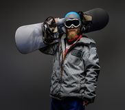Brutal man with a red beard wearing a full equipment holding a snowboard on his shoulder, isolated on a dark background. A brutal man with a red beard wearing a royalty free stock photo