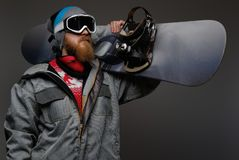 Brutal man with a red beard wearing a full equipment holding a snowboard on his shoulder, isolated on a dark background. A brutal man with a red beard wearing a stock photos