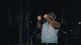 A strong bodybuilder makes triceps exercises with a chain in the gym. stock video footage