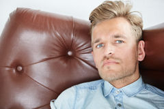 Brutal man in a shirt with short sleeves sitting in the brown chair Royalty Free Stock Photos