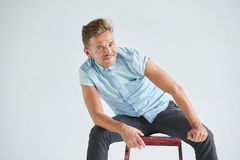 Brutal man in a shirt with short sleeves sitting in the chair , Royalty Free Stock Photos