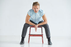 Brutal man in a shirt with short sleeves sitting on a red chair Royalty Free Stock Photo