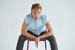 Brutal man in a shirt with short sleeves sitting on a red chair Royalty Free Stock Images