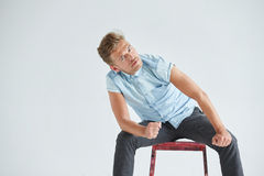 Brutal man in a shirt with short sleeves sitting on a red chair Stock Image
