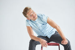 Brutal man in a shirt with short sleeves sitting on a red chair Royalty Free Stock Photography