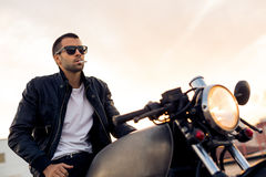 Brutal man sit on cafe racer custom motorbike. Beautiful happy rider man with beard and mustache in black biker jacket, denim and fashion sunglasses smoking stock photo