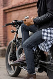 Brutal man sit on cafe racer custom motorbike. Close up of a handsome rider biker man hand puts on a leather glove while sit on classic style cafe racer Royalty Free Stock Photo