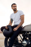 Brutal man sit on cafe racer custom motorbike. Stock Photo