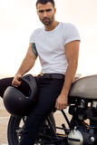 Brutal man sit on cafe racer custom motorbike. Close up of a handsome rider male in white blank t-shirt look to camera near classic style cafe racer motorcycle stock photography