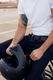 Brutal man sit on cafe racer custom motorbike. Close up of a handsome rider man in white blank t-shirt with helmet near classic style cafe racer motorcycle at stock images