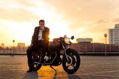 Brutal man sit on cafe racer custom motorbike. Handsome fit rider guy with beard and mustache in black leather biker jacket sit on classic style cafe racer stock photo