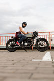 Brutal man sit on cafe racer custom motorbike. Handsome happy rider guy in red sneakers and black moto helmet look to camera sit on his classic style biker cafe royalty free stock photos