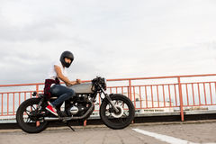 Brutal man sit on cafe racer custom motorbike. Handsome happy rider guy in red sneakers, white t-shirt and black moto helmet sit on his classic style biker cafe stock image
