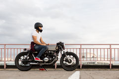 Brutal man sit on cafe racer custom motorbike. Handsome happy rider man in red sneakers, white t-shirt and black moto helmet sit on his classic style biker cafe stock photography