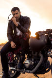 Brutal man sit on cafe racer custom motorbike. Handsome rider man with beard and mustache in black biker jacket put on sunglasses sit on classic style cafe stock photography