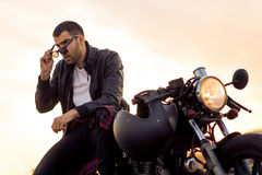 Brutal man sit on cafe racer custom motorbike. Handsome rider man with beard and mustache in black biker jacket take off sunglasses on classic style cafe racer royalty free stock images