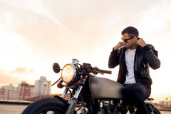 Brutal man sit on cafe racer custom motorbike. Handsome rider man with beard and mustache in black fashion sunglasses smoking cigaret and correct biker jacket royalty free stock image
