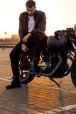 Brutal man sit on cafe racer custom motorbike. Handsome rider man with beard and mustache in black leather biker jacket, boot and jeans sit on classic style stock photo