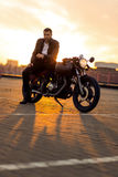 Brutal man sit on cafe racer custom motorbike. Handsome rider man with beard and mustache in black leather biker jacket sit on classic style cafe racer royalty free stock photo