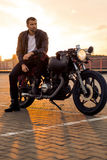 Brutal man sit on cafe racer custom motorbike. Handsome rider man with beard and mustache in black leather biker jacket sit on classic style cafe racer royalty free stock photography