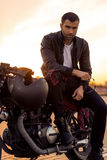 Brutal man sit on cafe racer custom motorbike. Handsome rider man with beard and mustache in black leather biker jacket sit on classic style cafe racer stock photography