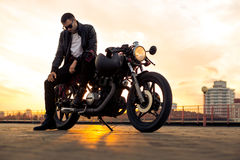 Brutal man sit on cafe racer custom motorbike. Handsome rider man with beard and mustache in black leather biker jacket and denim sit on classic style cafe royalty free stock image