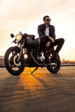 Brutal man sit on cafe racer custom motorbike. Royalty Free Stock Image