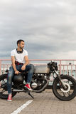 Brutal man sit on cafe racer custom motorbike. Handsome rider man with a beard and mustache sit on classic style biker cafe racer motorcycle and ready for long royalty free stock images