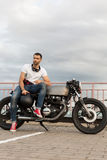 Brutal man sit on cafe racer custom motorbike. Handsome rider man with a beard and mustache sit on classic style biker cafe racer motorcycle and and wait royalty free stock photography