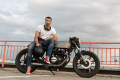 Brutal man sit on cafe racer custom motorbike. Handsome rider man with a beard and mustache sit on classic style biker cafe racer motorcycle and and wait his stock images