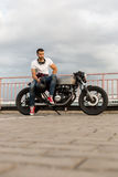 Brutal man sit on cafe racer custom motorbike. Handsome rider man with beard and mustache in red sneakers and black moto glasses sit on classic style biker cafe stock image