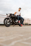 Brutal man sit on cafe racer custom motorbike. Handsome rider man with beard and mustache in red sneakers sit on classic style biker cafe racer motorcycle look royalty free stock photography