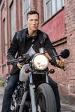 Brutal man sit on cafe racer custom motorbike. Handsome rider biker man in black leather jacket sit on classic style cafe racer motorcycle and look forward stock photos